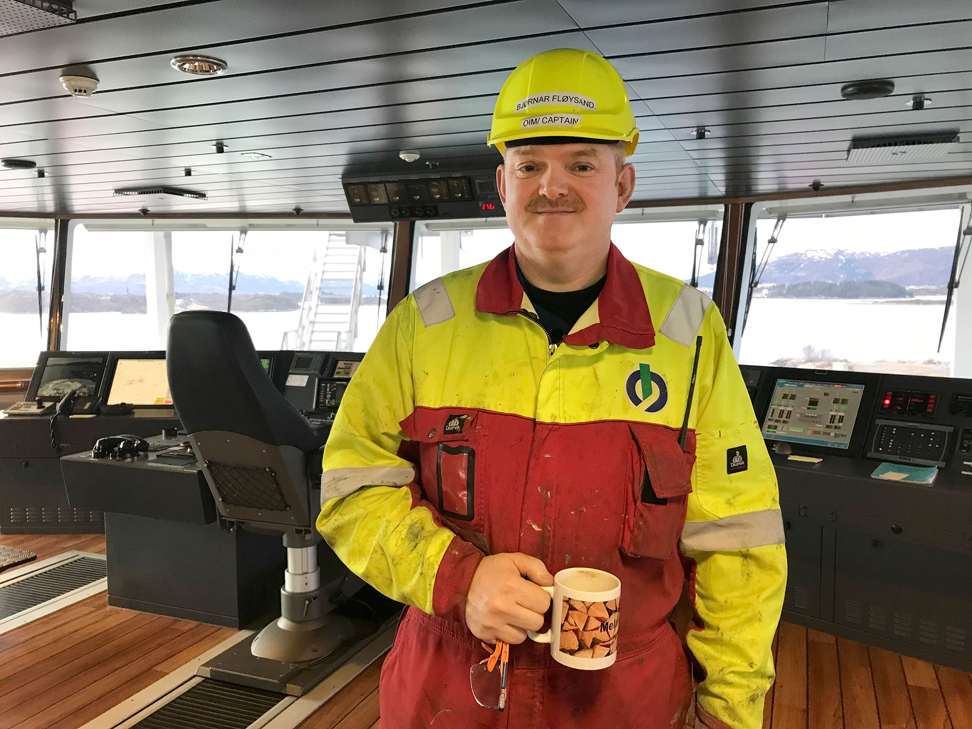 The captain on the bridge, the only interior area in which work overalls are accepted.